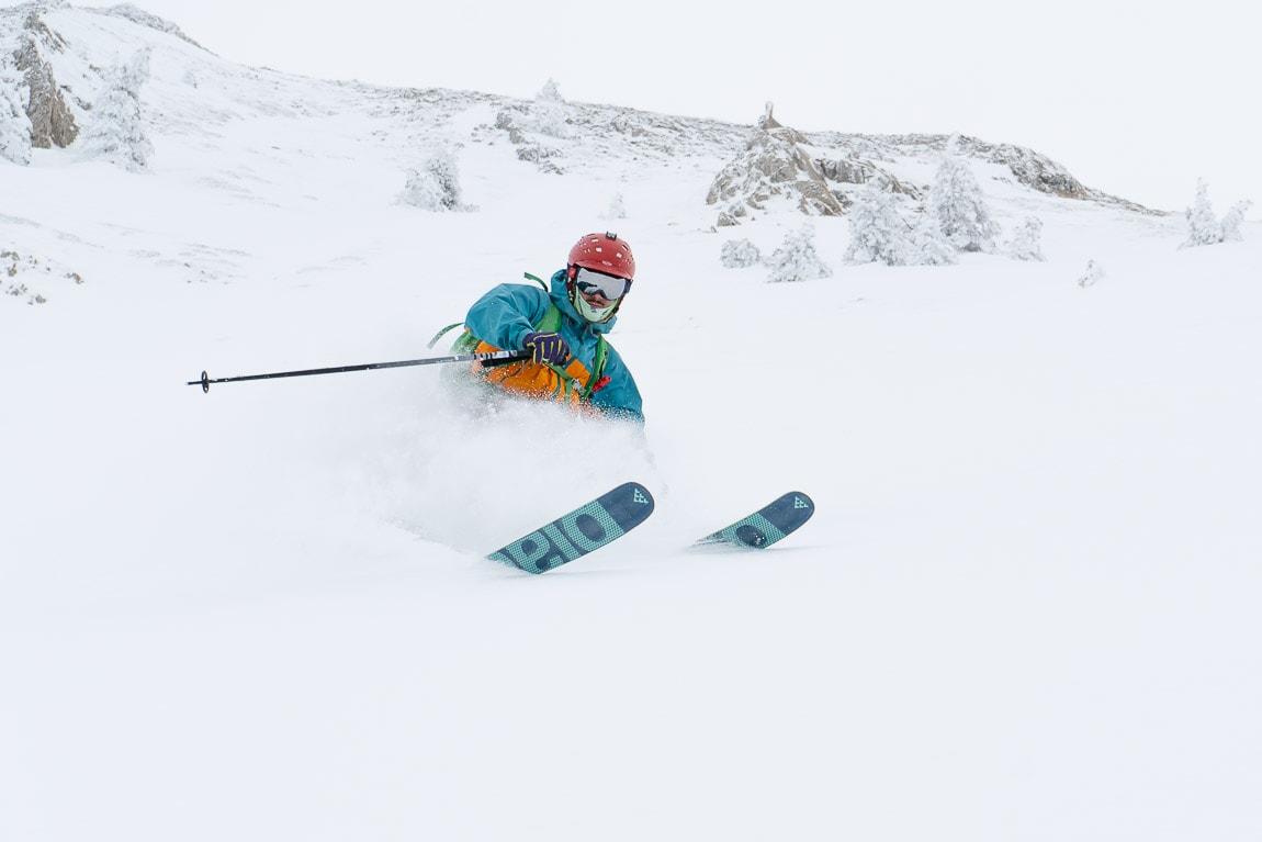 Esquiador con esquís black crows atris, casco rojo y nieve hasta la cintura